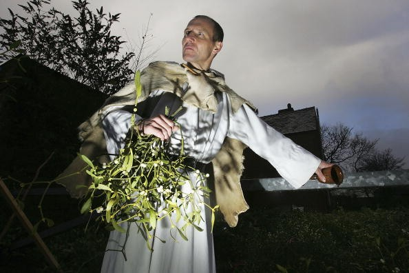 TENBURY WELLS, UNITED KINGDOM - DECEMBER 06: Druid Mark Graham blesses this years crop of mistletoe and annoints it with mead at Tenbury Wells Market, on December 6, 2005, Tenbury Wells, England. Ancient druids believed mistletoe had magical properties because of the way it grows, never touching the ground and without taking nourishment from the earth. Tenbury Wells has been the traditional mistletoe capital for over 150 years. Druids blessed this years crop before buyers put their bids in for the festive plant. Many buyers fear it could be the last ever auction on the site as the land has been sold off for development. The tradition of kissing under the mistletoe at Christmas comes from the belief that mistletoe has fertility magic.