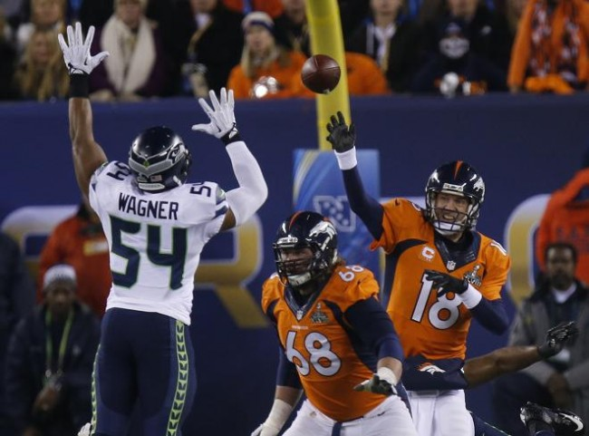 Denver Broncos quarterback Peyton Manning (R) throws a pass past Seattle Seahawks Bobby Wagner (L) and teammate Zane Beadles in the second quarter  in the NFL Super Bowl XLVIII football game in East Rutherford, New Jersey, February 2, 2014. (Reuters)