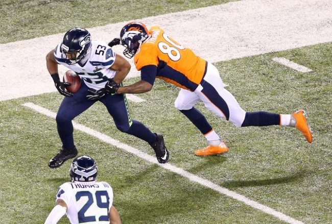 Seattle Seahawks outside linebacker Malcolm Smith (53) returns a fumble past Denver Broncos tight end Julius Thomas (80) in the third quarter in Super Bowl XLVIII at MetLife Stadium.