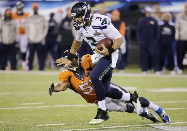Seattle Seahawks quarterback Russell Wilson (3) breaks a tackle by Denver Broncos middle linebacker Paris Lenon during the third quarter  in the NFL Super Bowl XLVIII football game in East Rutherford, New Jersey, February 2, 2014.