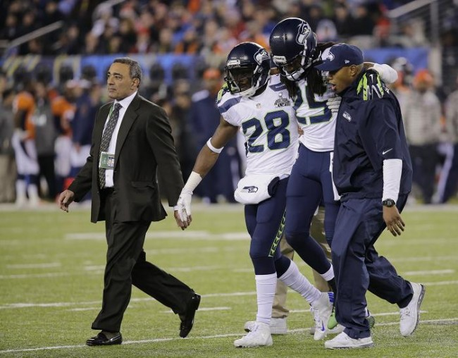 Seattle Seahawks cornerback Richard Sherman (25) is carried off the field by training staff and teammate Walter Thurmond after an injury while playing the Denver Broncos during the fourth quarter in the NFL Super Bowl XLVIII football game in East Rutherford, New Jersey, February 2, 2014. (REUTERS)