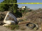 Police tape marks the upper boundary of a trash-filled ravine where Mexican federal agents are searching for the remains.
