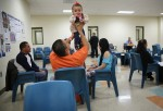 An immigrant detainee holds his daughter during a family visitation visit at the Adelanto Detention Facility on November 15, 2013 in Adelanto, California.
