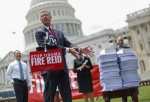 Rep. Doug Collins (R-GA) points to a stack of bills that passed the House of Representatives but have not been taken up by the Senate while calling for Senate Majority Leader Harry Reid (D-NV) to be 'fired' during a rally outside the U.S. Capitol July 29,