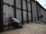 Family members reunite through bars and mesh of the U.S.-Mexico border fence at Friendship Park on November 17, 2013 in San Diego, California. The U.S. Border Patrol allows people on the American side to visit with friends and family through the fence on