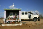 A transport van driver checks under his hood at a shrine where many immigrants stop to pray on the dirt toll road that leads to the border on June 6, 2006 near Altar, Mexico,