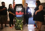 Members of United We Dream, Maria Palacios (2nd L) of Tampa, Florida, Yadira Dumet (3rd L) of New York City, and Greisa Martinez (R) of Dallas, Texas place a mock coffin outside the office of Sen. Roger Wicker (R-MS) during a protest July 21, 2014 on Capi