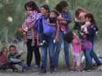 Central American immigrants await transportation to a U.S. Border Patrol processing center after crossing the Rio Grande from Mexico into the Texas on July 24, 2014 near Mission, Texas. Tens of thousands of undocumented immigrants, many of them families o