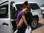 A mother and child, 3, from El Salvador await transport to a processing center for undocumented immigrants after they crossed the Rio Grande into the United States on July 24, 2014 in Mission, Texas. Tens of thousands of immigrant families and unaccompani